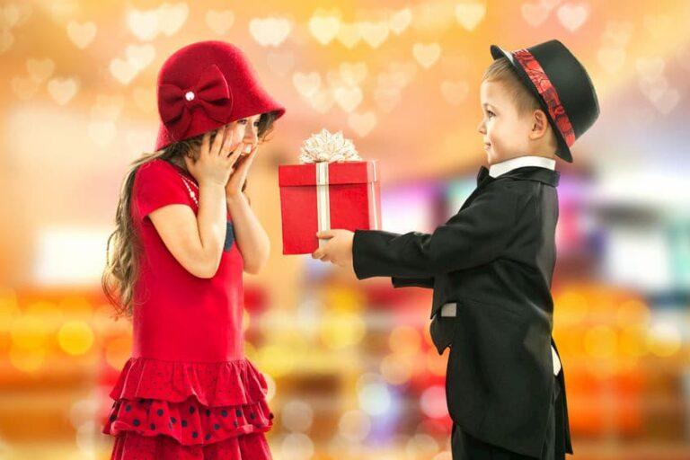 Bimbo che dona un pacchetto regalo a una bimba